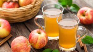 jabukovo sirće i mnogo jabuka na stolu.