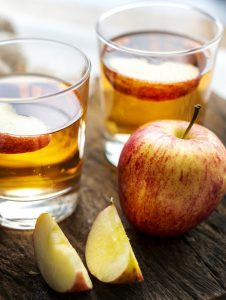 jabuka i dvije čaše jabukovog sirćeta.