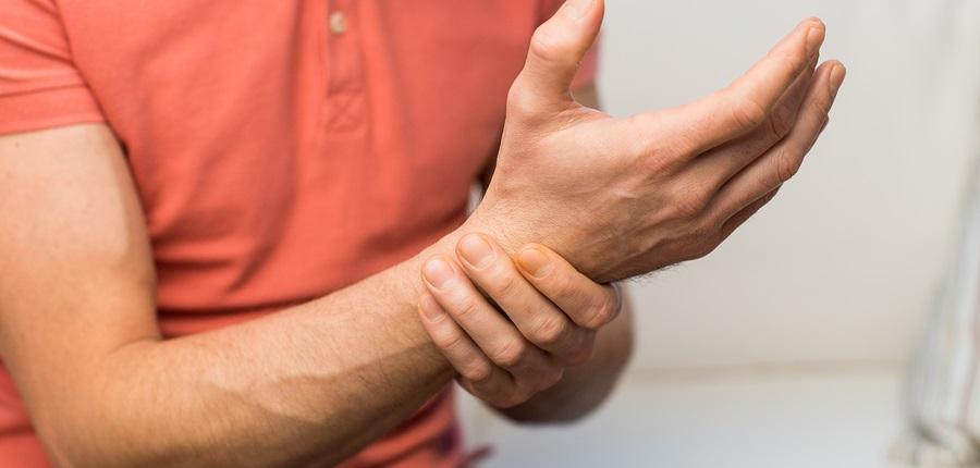 čovjek se drži za zglob desne ruke.