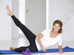 žena srednjih godina vježba na podu.